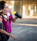 Young sportswoman drinking water (or energy drink) during rest period of morning cardio session. She is sitting on the stairway with smart phone attached to her arm and white headphones around her neck.
