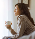 Young woman looking over window pane holding coffee. Thoughtful woman thinking and looking away while drinking hot tea. Woman in warm sweater looking outside window while drinking tea at morning.