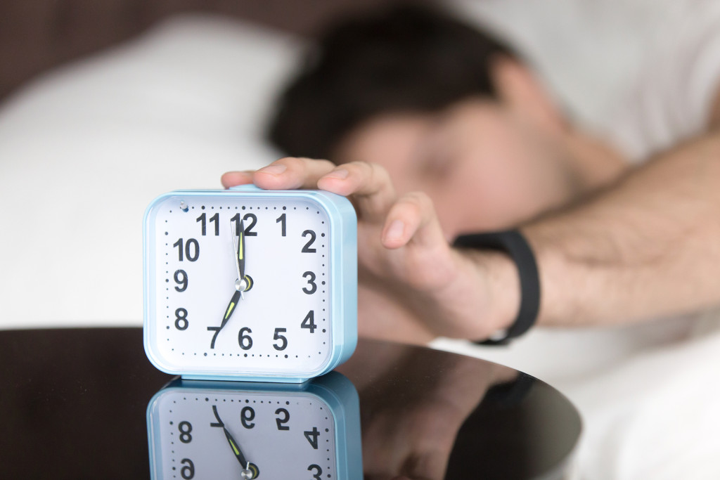 Young man sleeping alone is woken by alarm clock signal in the morning. Awaking guy trying to turn off ringing alarm by the hand still lying in bed at home. Daily alarm telling its time to get up