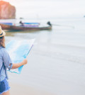 Young woman traveler with sky blue backpack and hat looking map at the sea with long boat thailand background from Ao Nang Beach Krabi. Traveling in Krabi Thailand Traveler summer concept