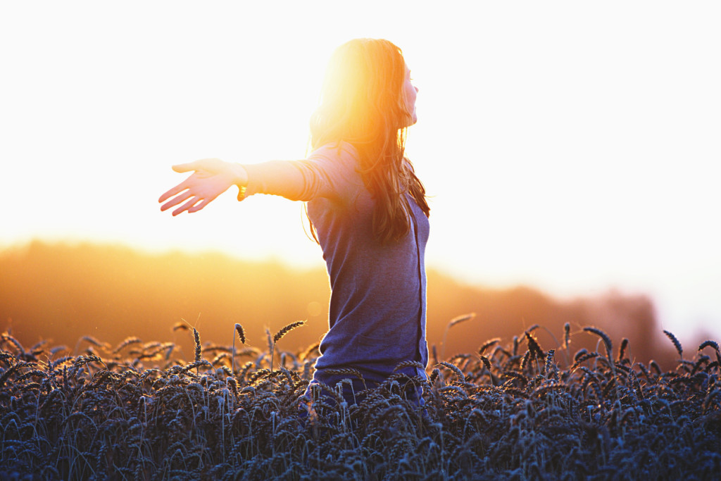 Young woman enjoying nature and sunlight in straw field