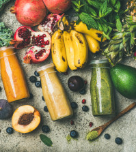 Flat-lay of colorful smoothies in bottles with fresh tropical fruit and superfoods on concrete background, top view. Healthy, clean eating, vegan, vegetarian, detox, dieting breakfast food concept