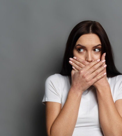 Keep silence. Scared woman covering mouth with hands looking away, speak no evil concept