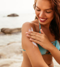 Young woman applying sunscreen lotion on the beach