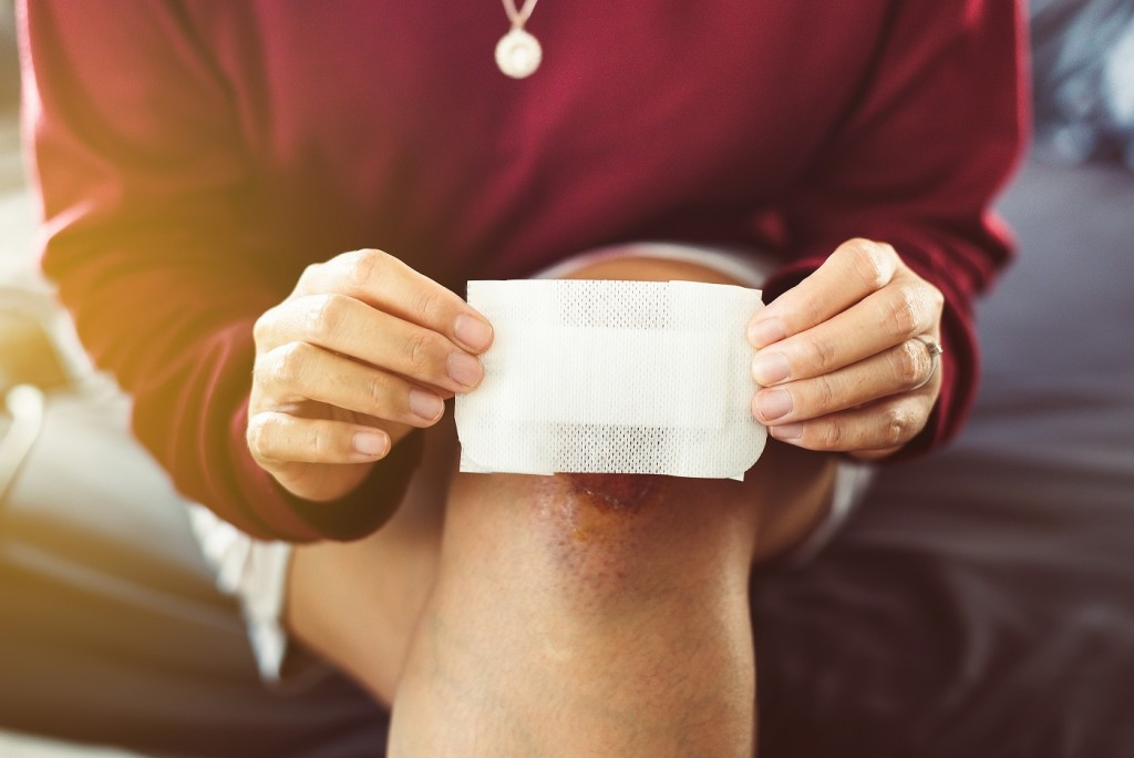 Woman using white patch for relieve wound on knee,Elastic bandaged
